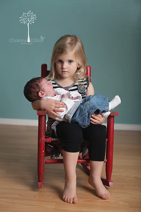 Big sister holds newborn baby brother