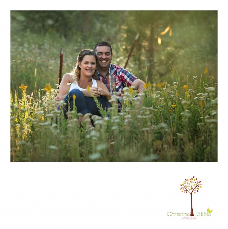 An engeged couple sit among a field of wildflowers while Sonora, CA engagement and wedding photographer Christine Dibble Photography takes their photos.