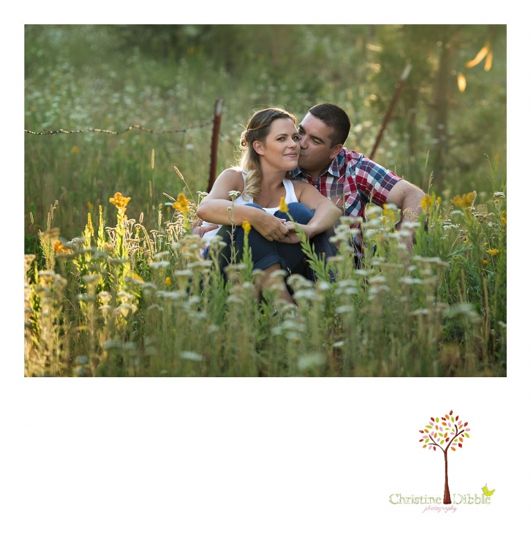 An engeged couple kiss among a field of wildflowers while Sonora, CA engagement and wedding photographer Christine Dibble Photography takes their photos.