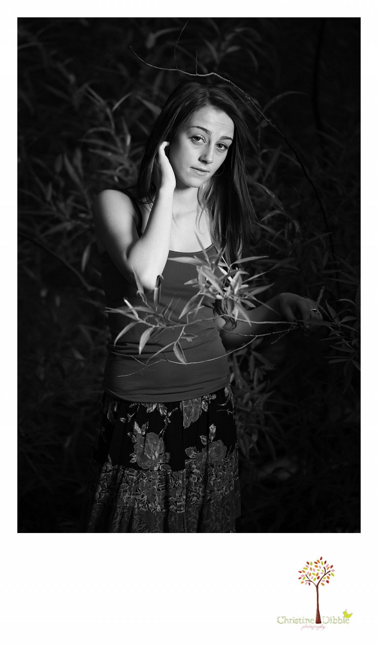 Sonora senior portrait photographer Christine Dibble Photography takes black and white photos outside with lights in a dark storm at Jeness Park in the Sierra Nevada Mountains near Cold Springs.