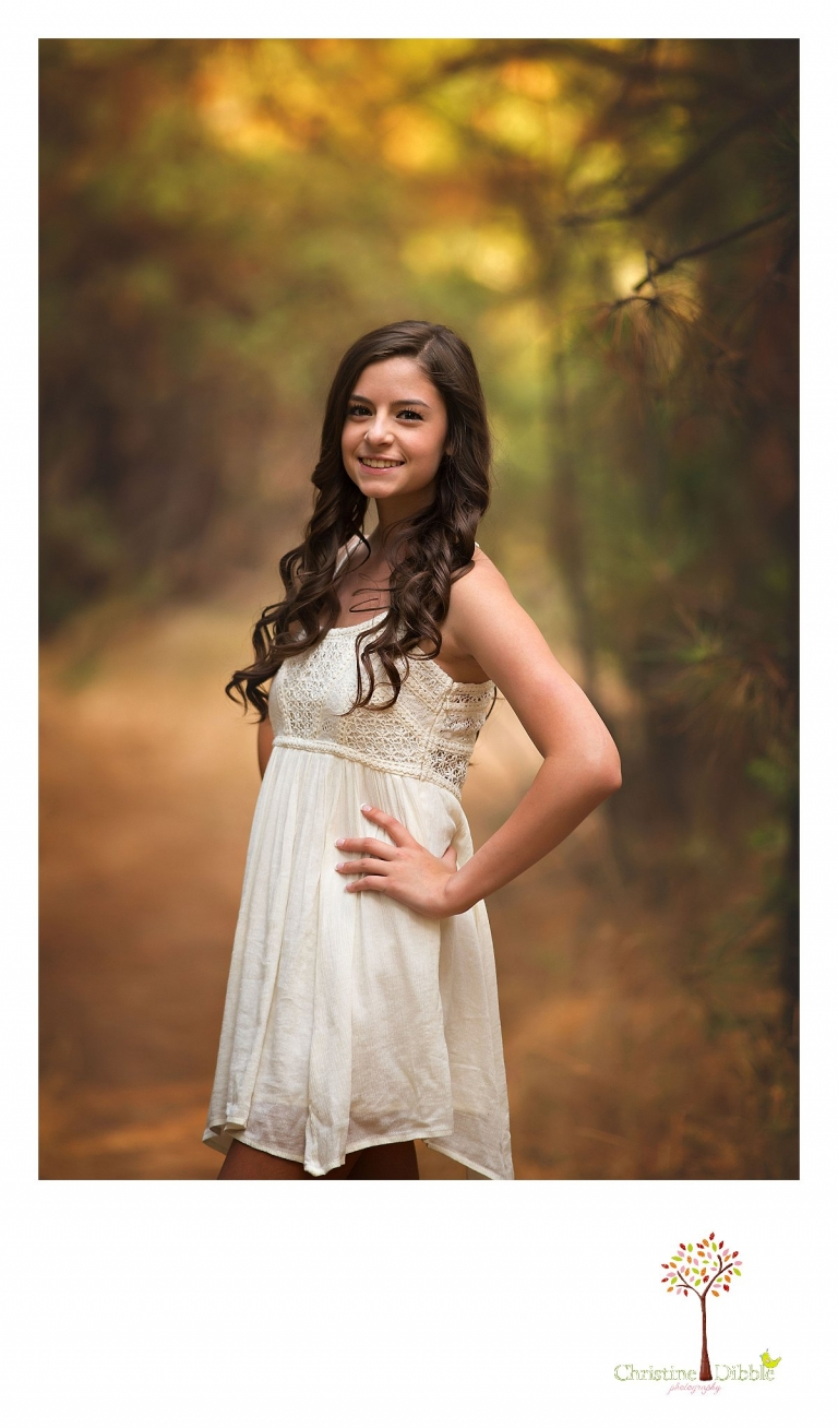 Sonora, Summerville and Turlock senior portrait photographer Christine Dibble Photography takes outdoor senior photos of a girl in a gauzy white dress in a grove of pine trees in a field near Twain Harte.