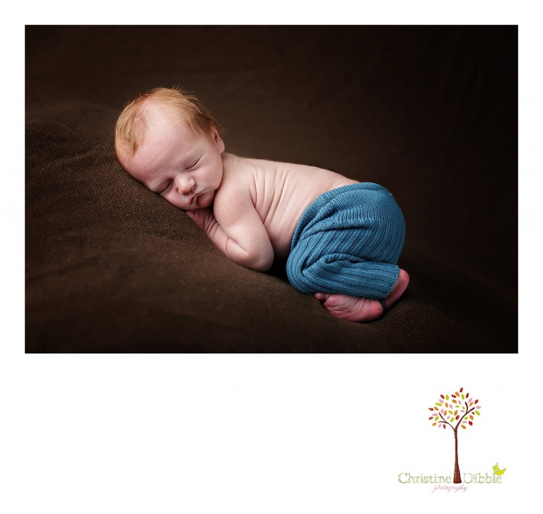 Best Sonora, CA newborn photographer Christine Dibble Photography takes studio photos of a baby boy as he sleeps in upcycled pants during his newborn photography session.