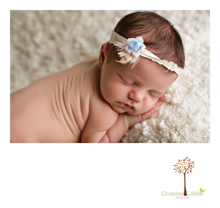 Sonora, CA newborn photography session by best Sonora newborn photographer Christine Dibble Photography includes photos of a baby girl wearing a flowered tie-back as she sleeps on a cream blanket.