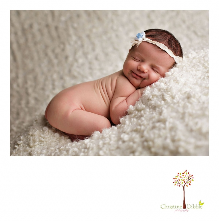 Sonora, CA newborn photography session by best Sonora newborn photographer Christine Dibble Photography includes a photo of a baby girl as she smiles in her sleep while wearing a flower headband.