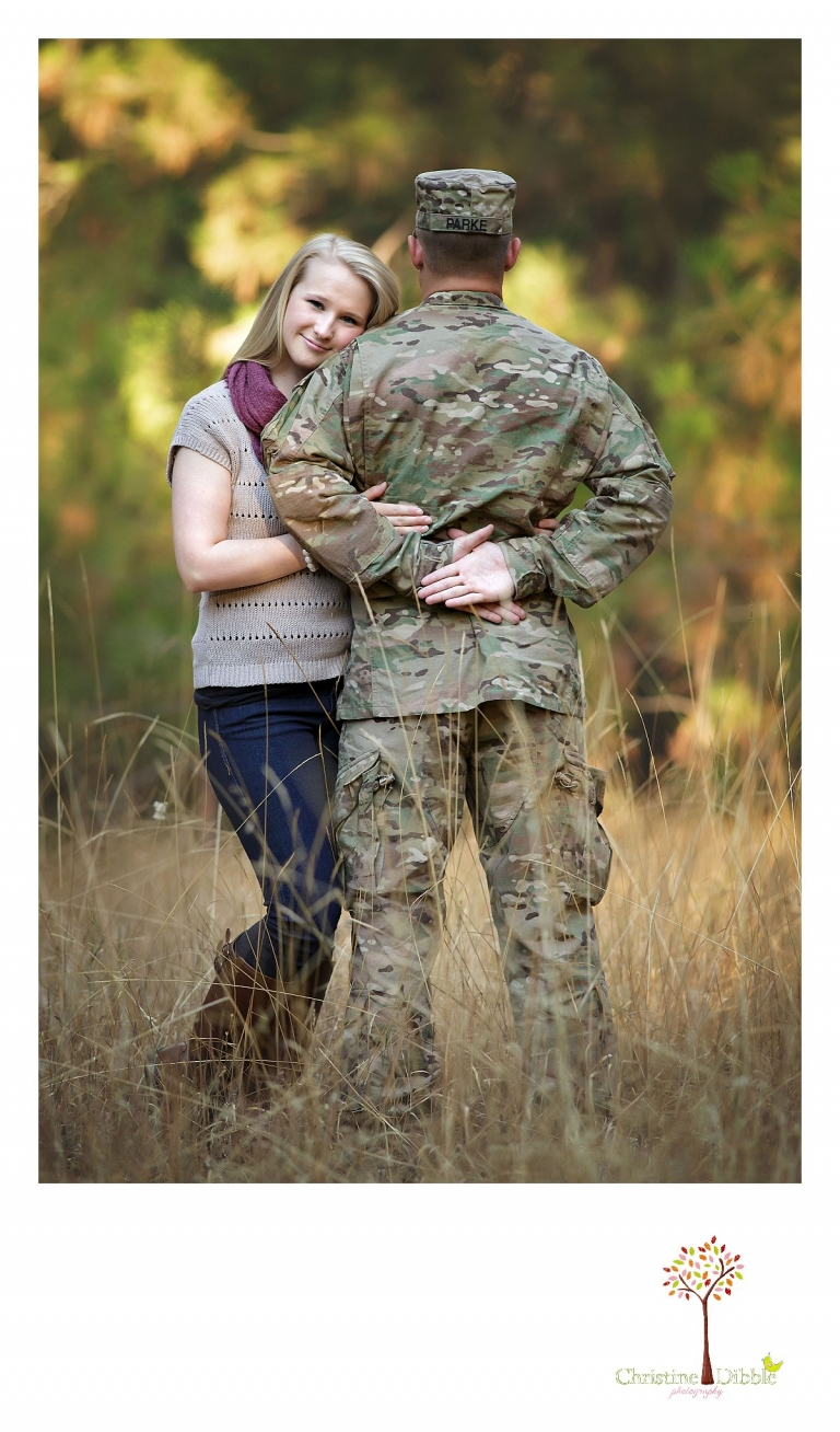Christine Dibble Photography of Sonora, CA takes couple's photos of a uniformed soldier on leave and his hometwon girlfriend as she hugs his arm for a photo in a field near Twain Harte.