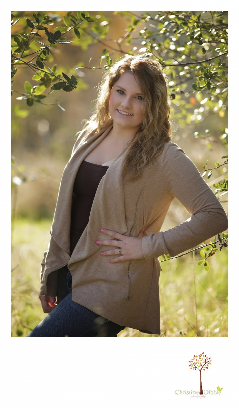 Sonora and Summerville High School senior portrait photographer Christine Dibble Photography takes outdoor photos of a beautiful senior girl in bushes with backlighting.