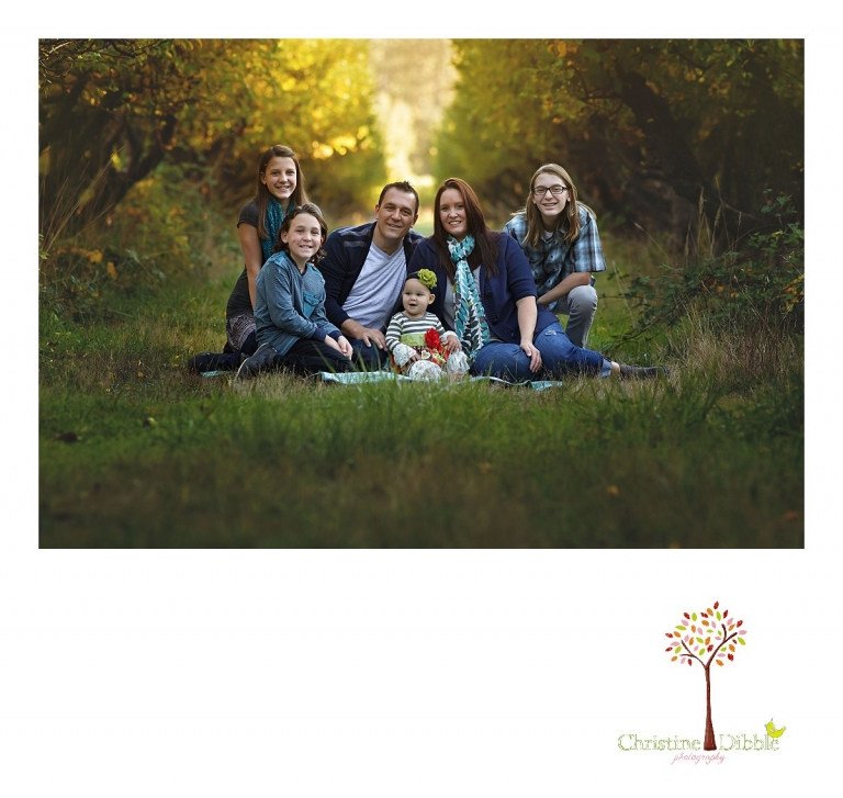 Indigeny Reserve photographer Christine Dibble Photography of Sonora takes family photos of a family with four children as they sit among the fall-colored apple orchard rows.