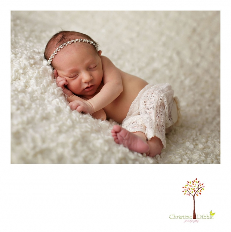 An eight day old newborn baby girl sleeps while Sonora newborn photographer Christine Dibble Photography takes portraits of her in a rhinestone tieback and upcycled pants.