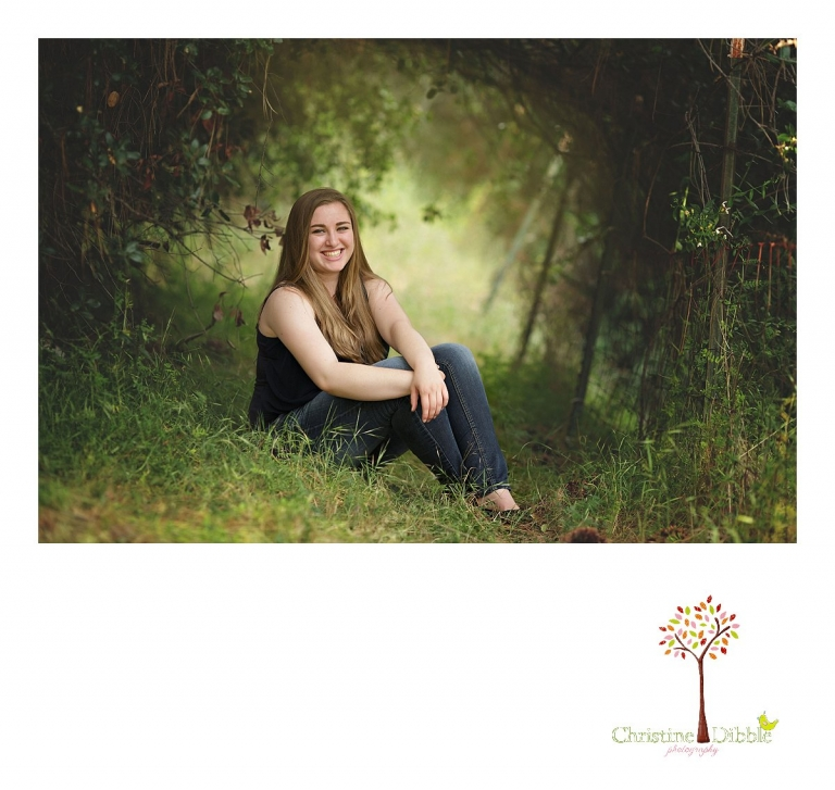 Sonora High senior portrait photographer Christine Dibble Photography takes outdoor portraits in rich color of a senior girl in a wooded tunnel that is backlit.