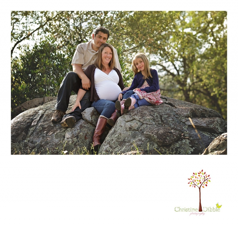 Sonora maternity photographer Christine Dibble Photography takes family portraits of a mother-to-be with her husband and daughter as they sit on granite rocks.
