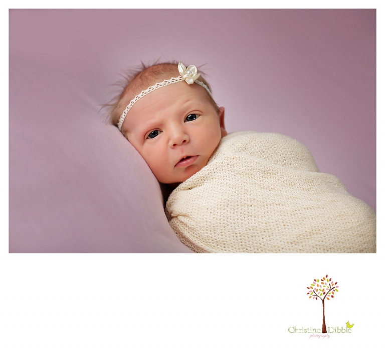 Sonora newborn photographer Christine Dibble Photography takes photos of a baby girl while she is wide awake in wraps and a headband.