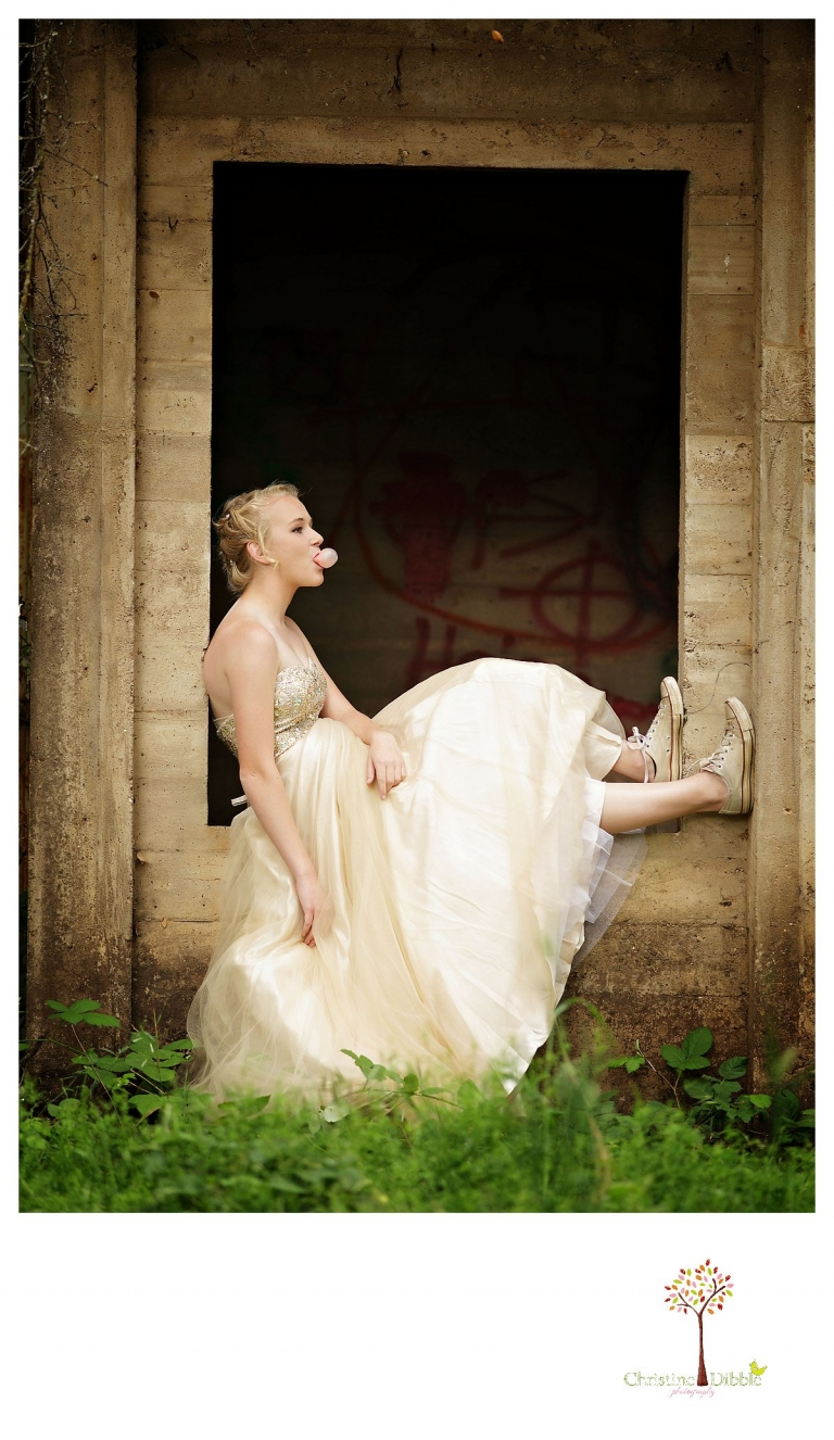 Sonora senior portrait photographer Christine Dibble Photography takes portraits of an eighth grade graduate in a formal gown and Converse shoes as she sits in the window of an abandoned house and blows a giant bubble.