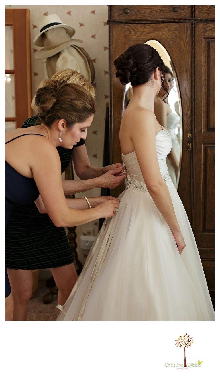 Sonora wedding photographer Christine Dibble Photography photographs a Twain Harte Tree Farm wedding as the bride dresses.