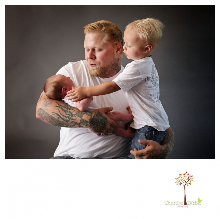 Sonora newborn and family photographer Christine Dibble Photography takes a portrait of a big brother reaching out to calm his crying newborn baby brother while dad helps during a newborn and family portrait session in the Sonora studio.