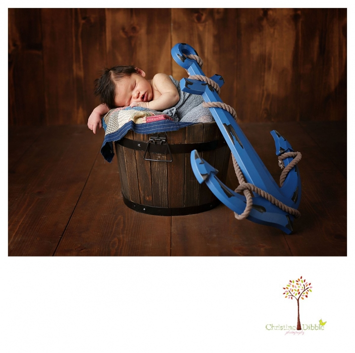 Newborn photography by best Sonora newborn photographer Christine Dibble Photography takes studio portraits of a baby boy sleeping in a bucket with an anchor prop from his nursery.