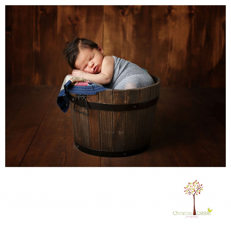 Newborn photography by best Sonora newborn photographer Christine Dibble Photography takes studio portraits of a baby boy asleep in a wrap and a bucket.