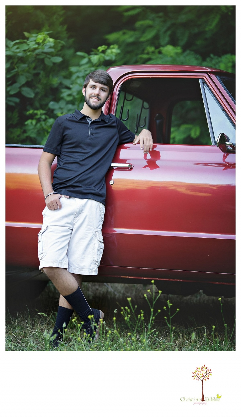 Sonora and Summerville senior portrait photographer Christine Dibble Photography takes senior portraits of a boy at Twain Harte Tree Farm as he stands beside his red Chevy truck.