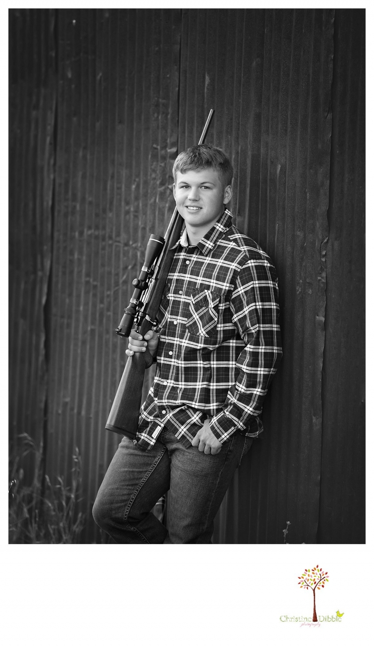 Summerville senior portrait photographer, Christine Dibble Photography of Sonora, takes a black and white portrait of a senior boy holding his hunting rifle as he leans on a rusted wall.