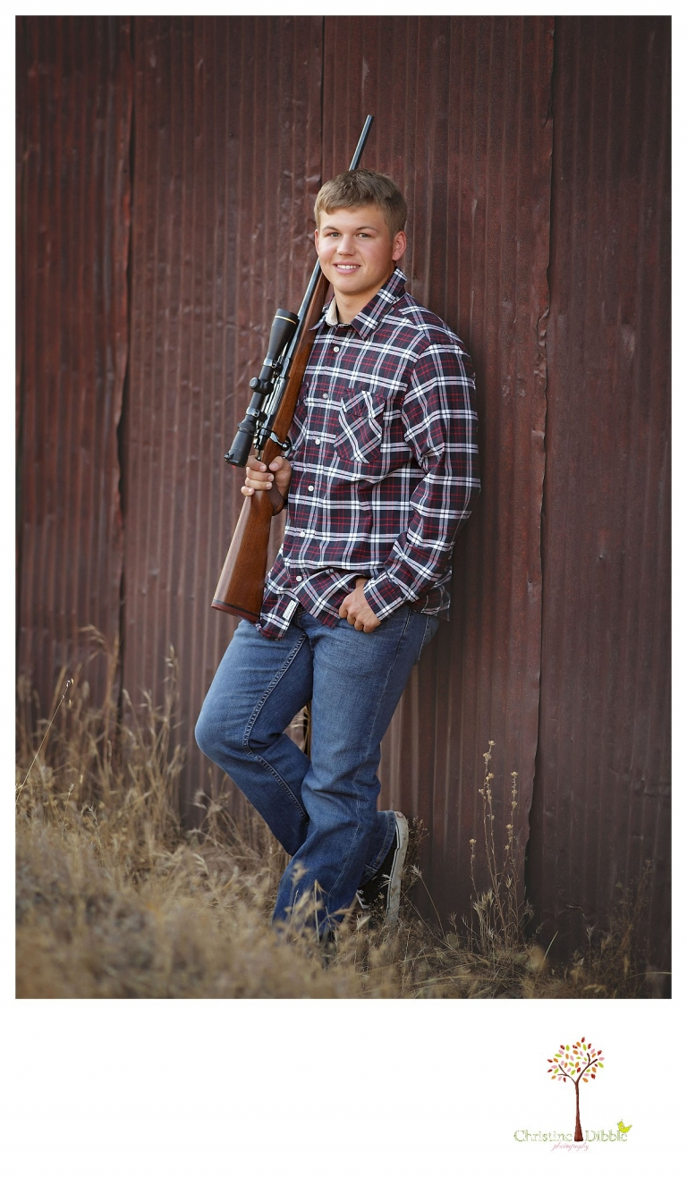 Summerville senior portrait photographer, Christine Dibble Photography of Sonora, photographs a senior boy with his hunting rifle as he wears a plaid shirt and jeans.