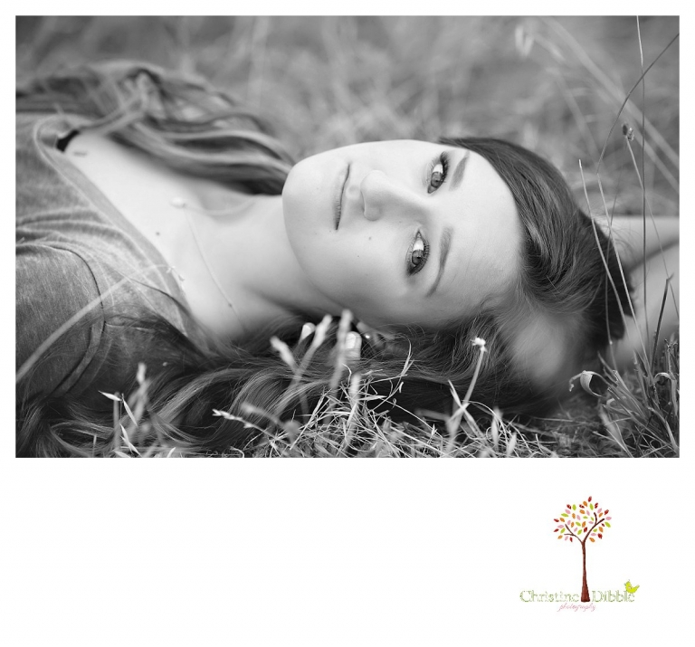 Summerville and Sonora senior portrait photographer Christine Dibble Photography takes photos of a senior girl lying in a grass field in black and white.