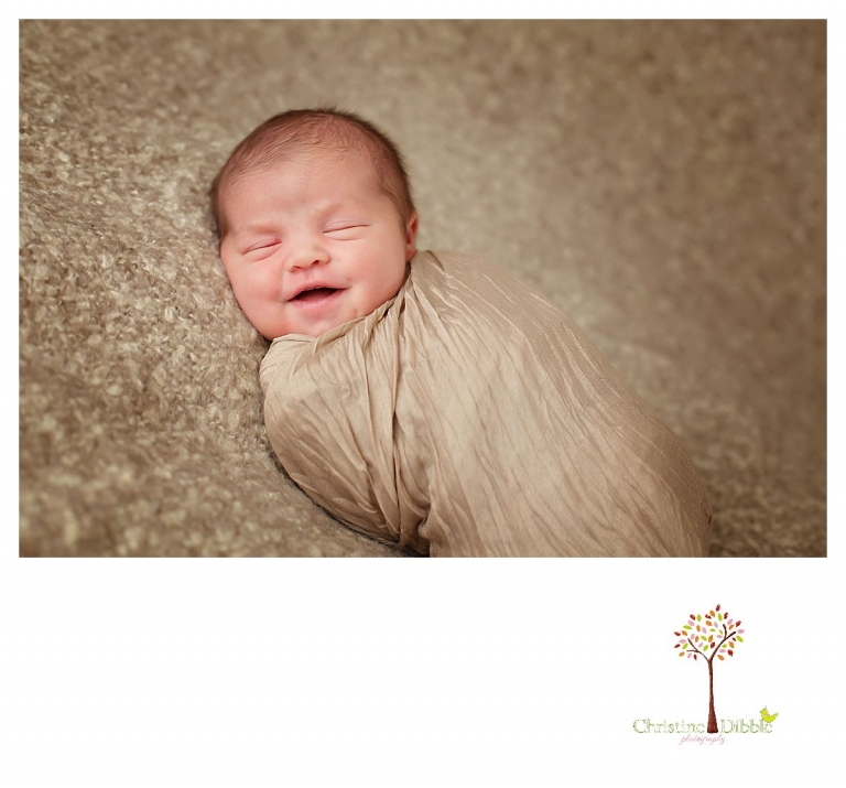 Newborn photography by Sonora photographer Christine Dibble Photography includes studio sessions with posed and prop images such as this smiling baby on a blanket.
