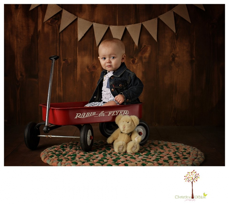 Sonora baby and child photographer Christine Dibble Photography takes first year portraits in her studio of a little boy with a red wagon and vintage accessories.
