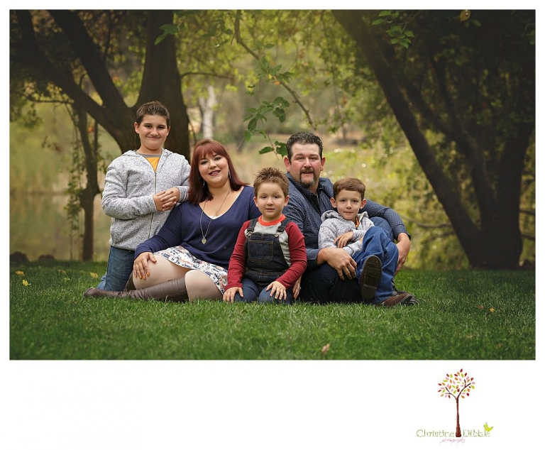Sonora family photographer Christine Dibble Photography takes family portraits in Angels Camp of a family with three boys on private property with olive trees and a pond.