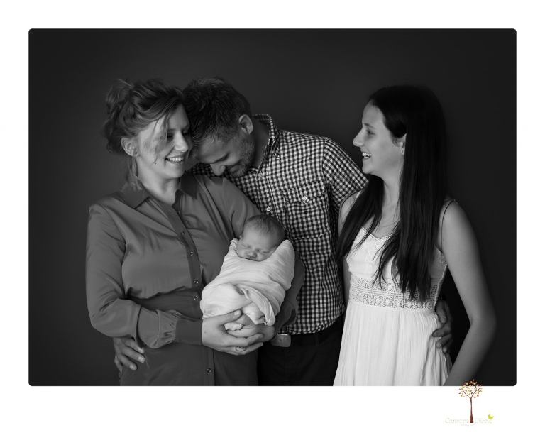 Best Sonora Newborn Photographer Christine Dibble Photography takes studio portraits of a baby sister with her parents and older sister and then posed newborn photos of baby alone.