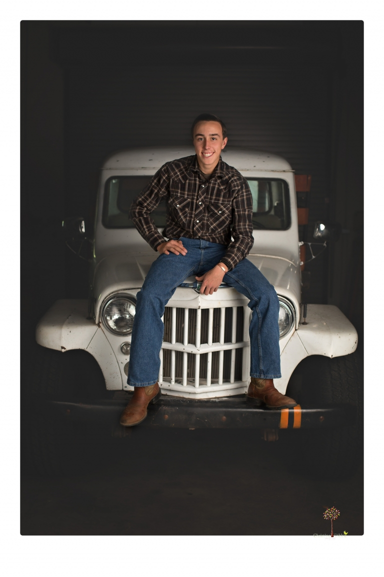 Summerville Senior Portraits taken by Christine Dibble Photography of Sonora in the auto shop with a senior boy's 1959 Jeep Willys pick-up truck and his letterman jacket.