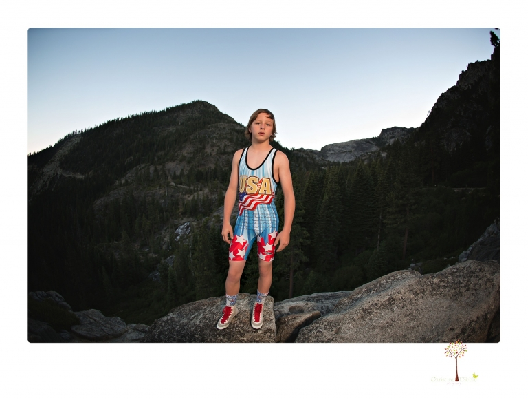 Sonora sports photographer Christine Dibble Photography takes wrestling portraits at Emerald Bay in Lake Tahoe of a wrestler on the cliffs looking over the falls and the bay at sunset with the full moon rising behind.