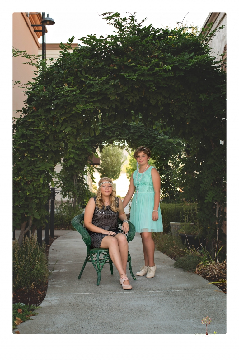 Sonora senior photographer Christine Dibble Photography takes portraits of two cousins dressed as flappers in Copperopolis Town Square before one leaves for college.