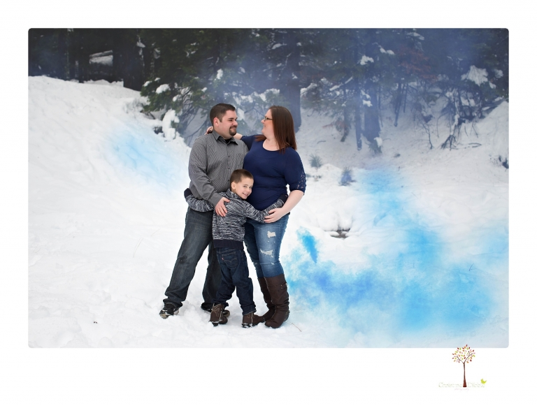 Sonora maternity photographer Christine Dibble Photography photographs a gender reveal session with colored smoke bombs in Long Barn in the snow.