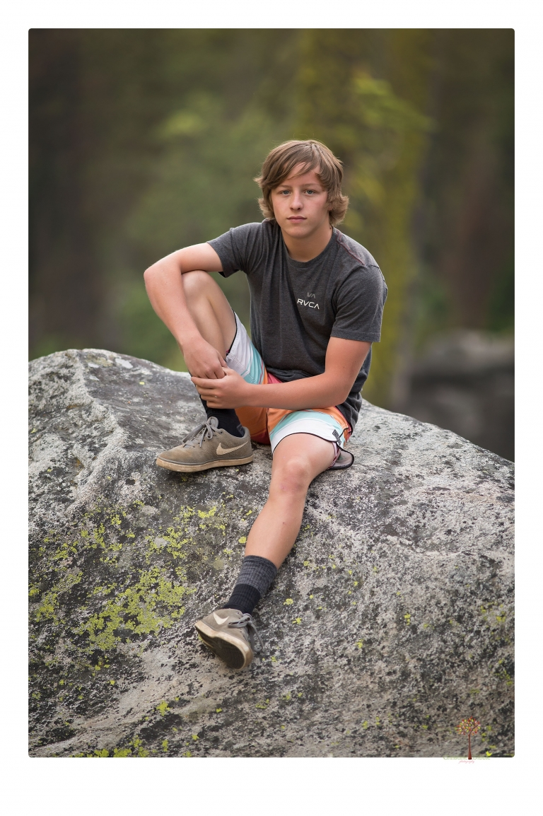 Summerville High School Senior portrait photographer Christine Dibble Photography takes four wheeling senior portraits of a boy with his trap gun, letterman jacket, and Toyota 4Runner as he drives over rocks and dives off cliffs.